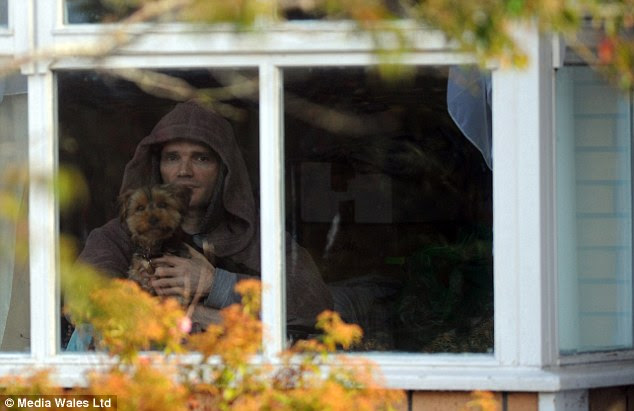 Mr Lloyd, pictured from outside his home with his dog Iggy Pop, now faces eviction from his home after his landlord became disgruntled that he had not been heating the house in St Fagans, Cardiff
