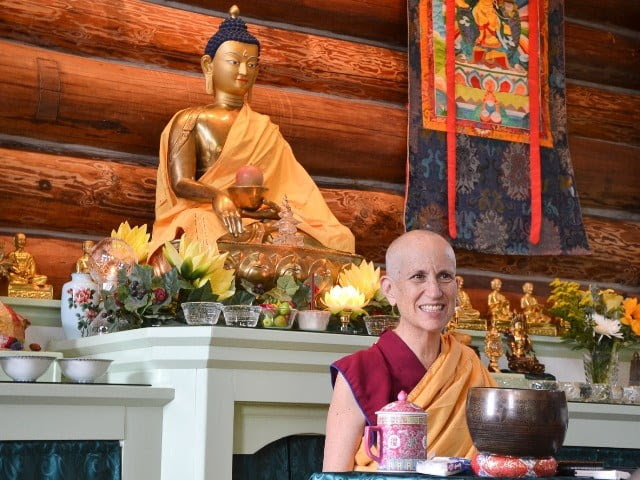 Venerable Thubten Chodron seated before the Buddha while she teaches.