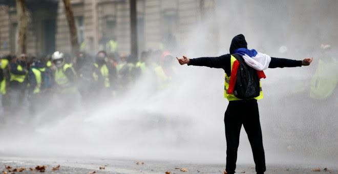 Un manifestante de los chalecos amarillos desafía a los antidisturbios durante las protestas en la Plaza de l'Etoile en París.- Stephane Mahe/REUTERS