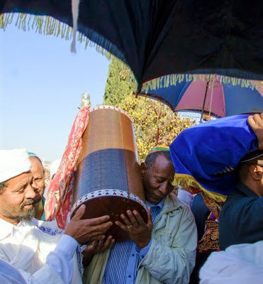 An Ethiopian Jewish                   man and a Kes, a religious leader of the Ethiopian                   Jews, carry the Torah.