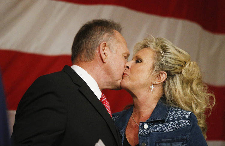 Alabama Senate candidate Roy Moore (R) kisses his wife, Kayla, during a campaign rally Tuesday night in Fairhope, Ala. (Brynn Anderson/AP)
