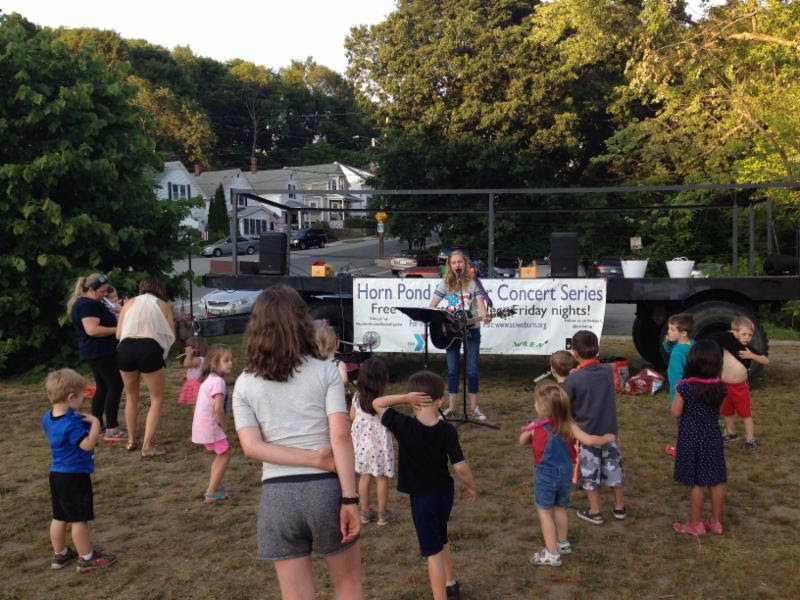 Children dancing and enjoying the summer concert at Horn Pond.