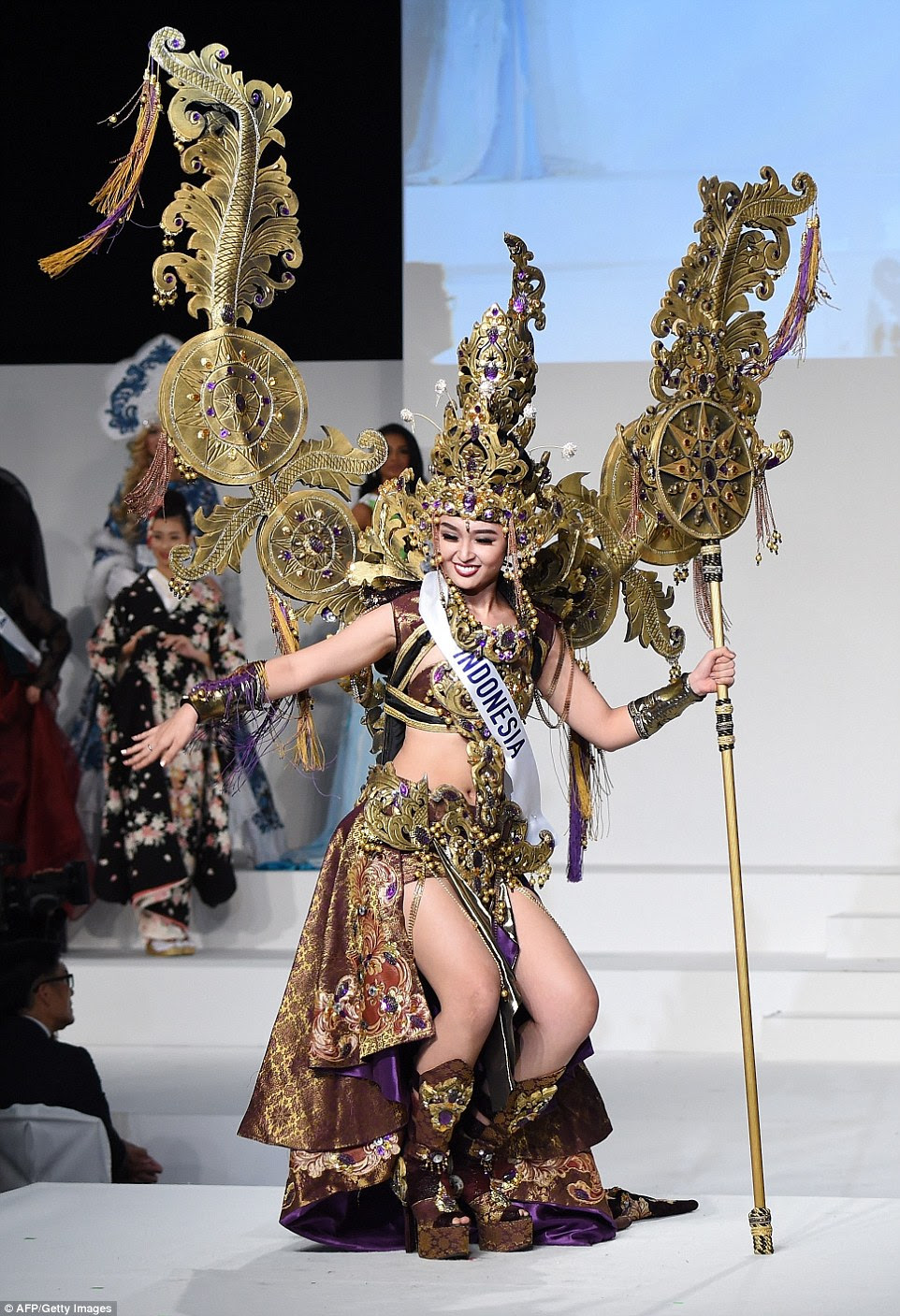 Another intricate costume came from Miss Indonesia, Chintya Fabiola. Inspired by the traditional dress worn by folk dancers, Chintya made a few moves herself, using her embellished staff as a prop. Her tall gold headdress was complemented by two gold tassled 'wings', a collar, a belt, cuffs and shin-high platform boots