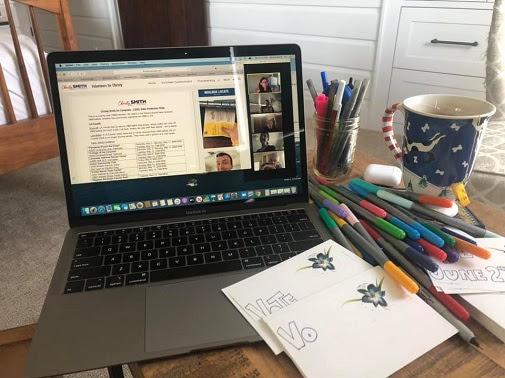 Postcarding supplies sit next to an laptop that displays a phonebanking call script.