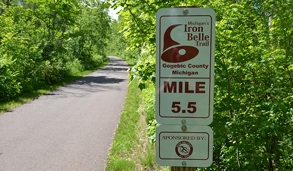 Paved trail with Iron Belle Trail sign
