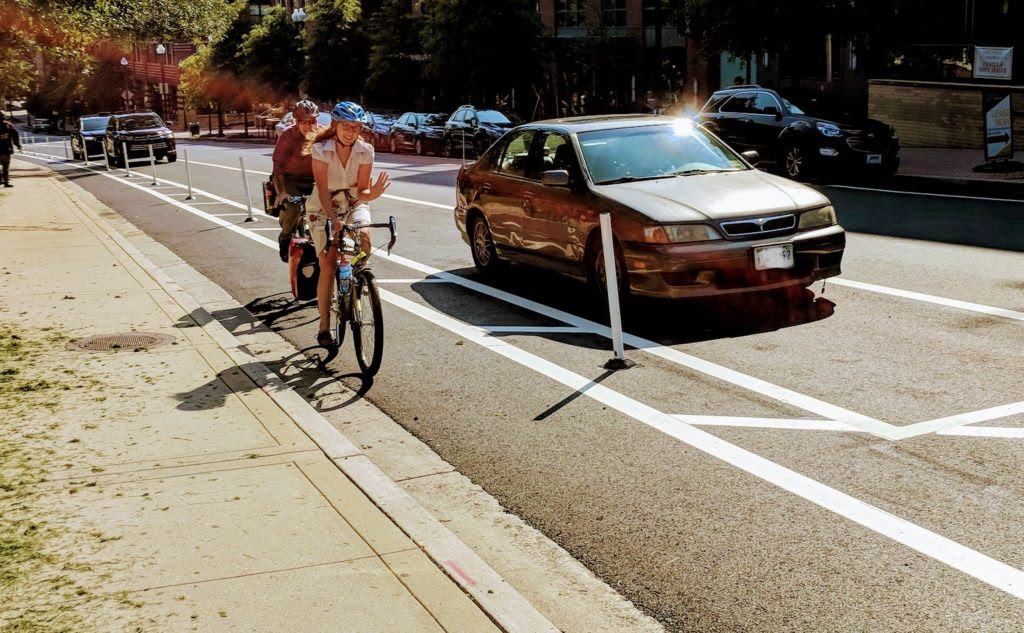 Two bicyclists riding in a protected bike lane in Arlington