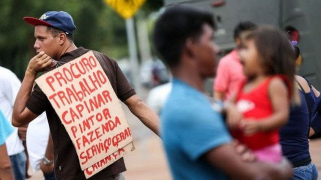 Homem com cartaz que diz 'procuro trabalho'