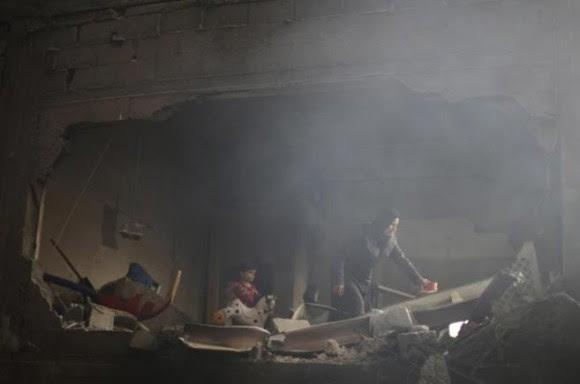 Una mujer palestina rebusca entre los escombros de lo que antes era su casa. Foto: Reuters.