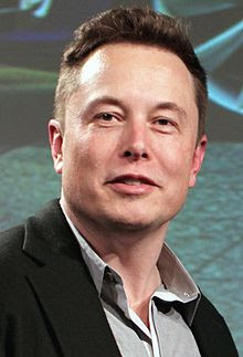 A close-up of Musk's face while giving a talk