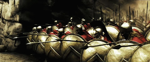 The Spartans align themselves in a tight formation of shields and spears pointed forward.