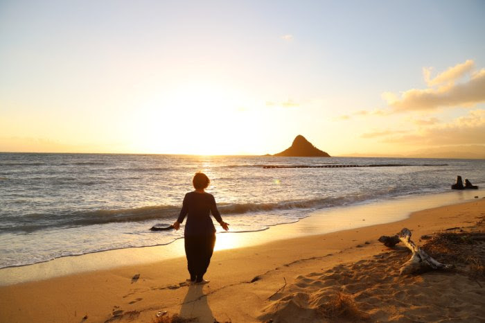 siloette image of Emma Kupu Mitchell with the sun rising behind her on a beach with an island mountain in the background