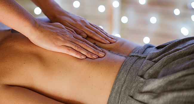 Hands massaging a client's lower back