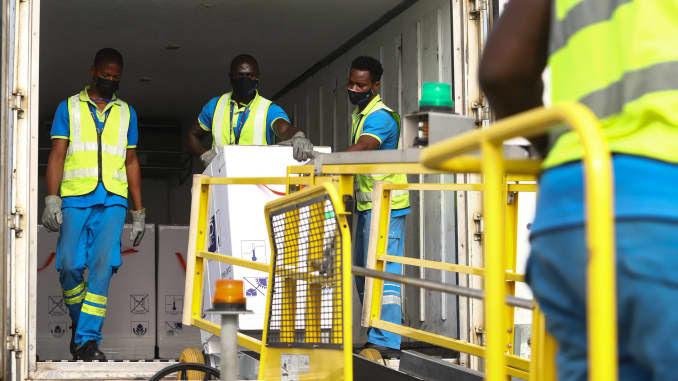 Funcionários do aeroporto descarregam um carregamento de vacinas Covid-19 do programa global de vacinação Covid-19 da Covax, no Aeroporto Internacional de Kotoka em Acra, em 24 de fevereiro de 2021.