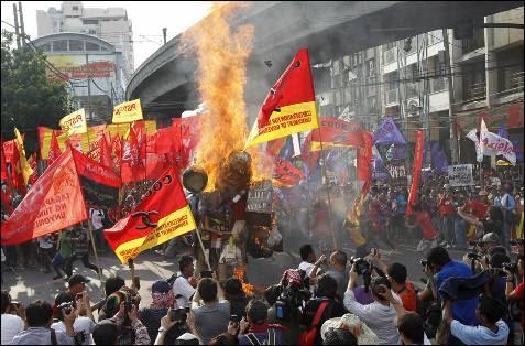 Trabajadores filipinos queman una efigie del presidente Benigno Aquino durante las protestas