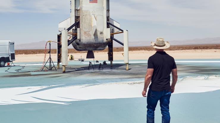 Jeff Bezos looks at a rocket booster on the landing pad
