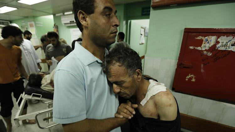 A Palestinian hugs his father who was wounded in an Israeli strike on a compound housing a UN school in Jabaliya refugee camp in the northern Gaza Strip, following their arrival at the Kamal Edwan hospital in Beit Lahia on July 30, 2014