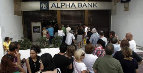 Ciudadanos haciendo cola para sacar dinero de un cajero automático. EFE/EPA/ALEXANDROS VLACHOS