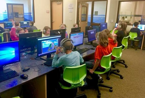 A classroom full of elementary students sit at computers playing games that teach coding.