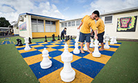 Kids playing giant chess outdoors