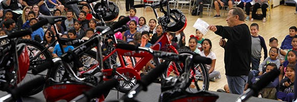 Numerous Central School third grade students smile and scream with excitement when told that they will all be receiving free bicycles thanks to a generous donor.