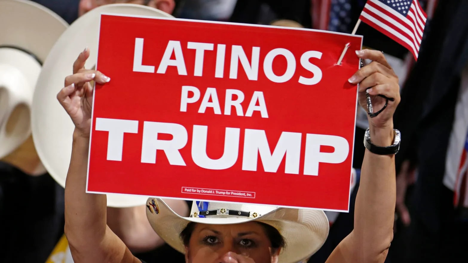 A woman at a rally for Trump holding a sign reading ''Latinos Para Trump''