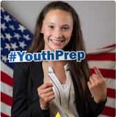 Youth student holding a #YouthPrep sign with left pointer finger pointing to sign