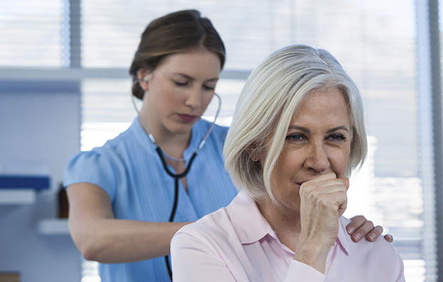 A senior woman coughing while a doctor listens with a stethoscope.