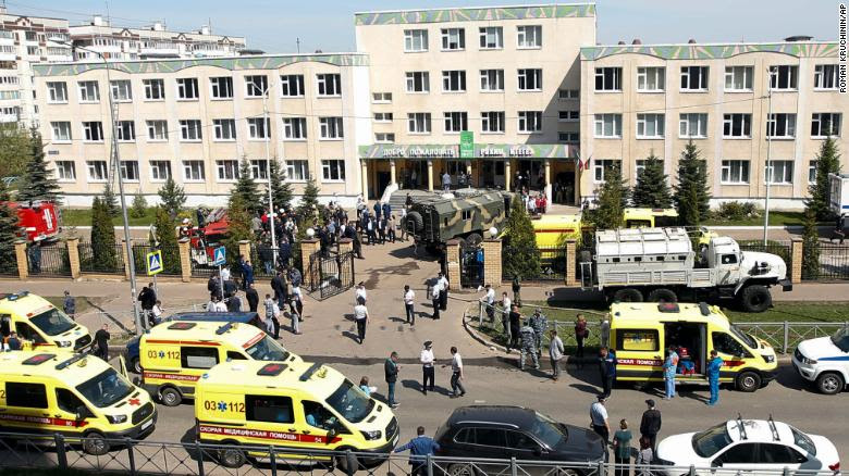 Multiple ambulances and police vehicles are seen outside of the Russian school where the shooting took place