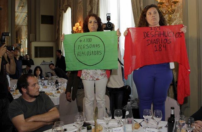 El dipuado de la CUP David Fernández observa a las dos activistas de la PAH que muestran en silencio pancartas contra los desahucios durante la intervención de Cañete.