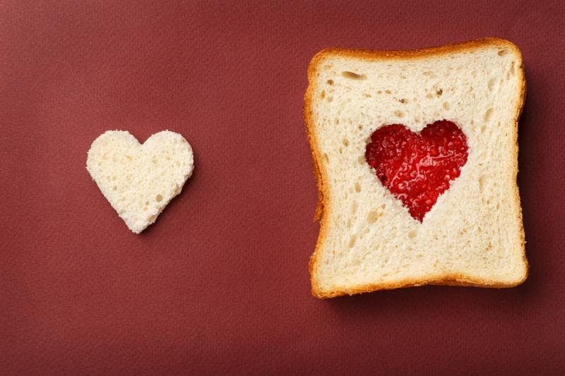 The composition of Valentine s Day. Left side  heart from white bread the right side  sandwich with red heart of raspberry jam. All this rests on a red background.