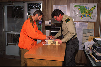 Al Stewart talks with a customer at the DNR office in Rose Lake.