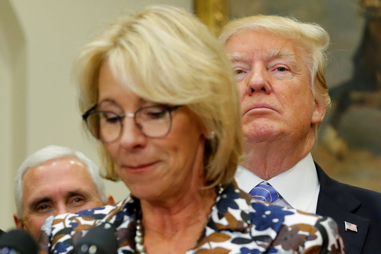 Donald Trump listens as Education Secretary Betsy DeVos speaks to students in May. (Jonathan Ernst/Reuters)