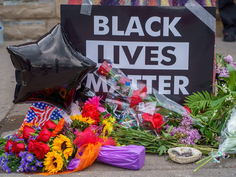 Image of a memorial for George Floyd on a sidewalk; various kinds of flowers and a balloon shaped like a black star are piled in front of a sign reading in black and white %22BLACK LIVES MATTER%22