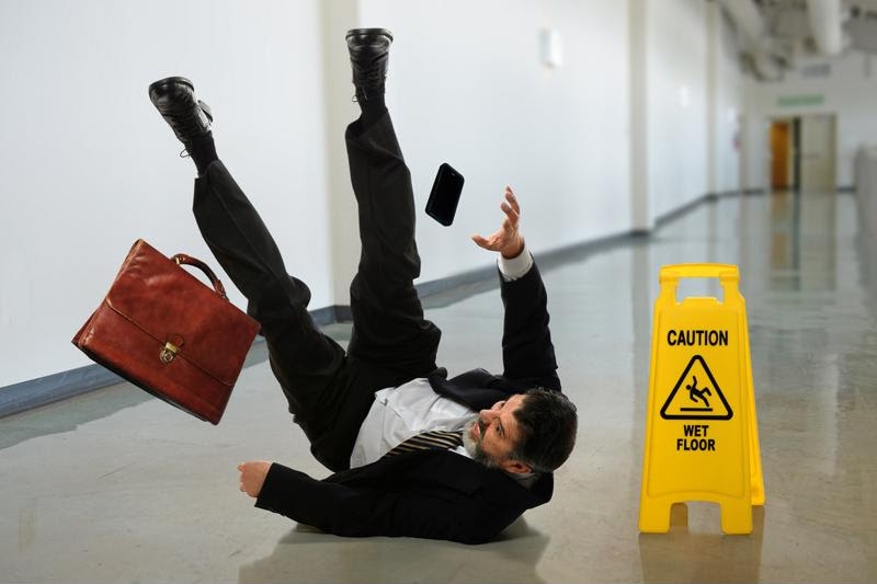 A businessman slips on an office floor.