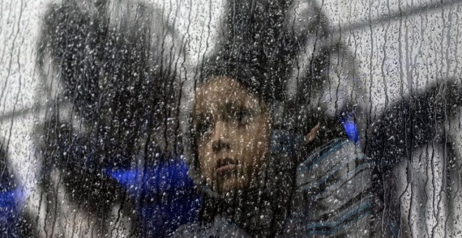 Una niña centroamericana que viaja en una caravana de migrantes, toma un autobús fuera de un refugio temporal en el este de Tijuana, México, el 6 de diciembre de 2018   Guillermo Arias/AFP