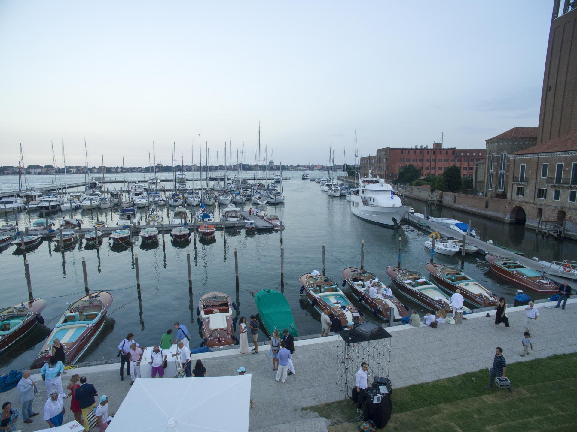 Cinema Santelena - una veduta panoramica del porto con tante barche parcheggiate ai moli, sulla destra si scorge una parte della città con mura antiche e tanta gente che cammina