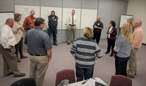 A dozen educators stand in a circle in the middle of a conference room for a facilitated discussion.