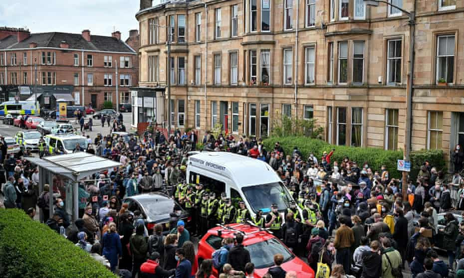 Protesters block the immigration enforcement van on Kenmure Street in Glasgow