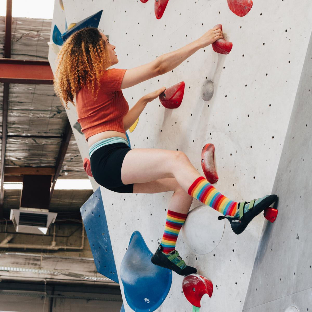 Person on rock climbing wall wearing rainbow socks