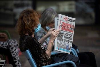 A woman reads Israel Hayom in Ramat Gan, October 14, 2020.