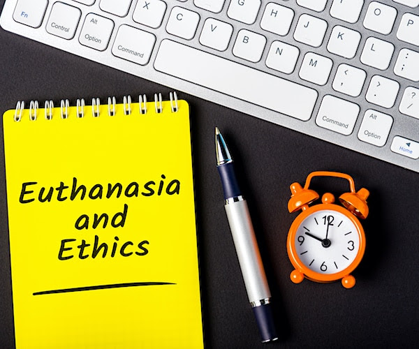 a graphic illustration with a computer keyboard, a pen, and a notepad that reads euthanasia and ethics