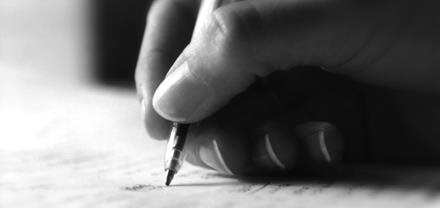 Photograph of a woman's hand grasping a pen, writing on paper.