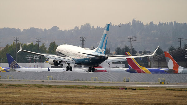 A Boeing 737 Max jet, piloted by Federal Aviation Administration chief Steve Dickson, flies past parked Boeing jets as it prepares to land at Boeing Field following a test flight in September.