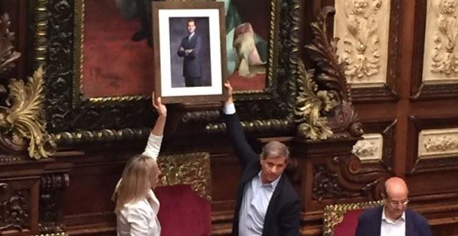 Momento en el que Fernández y Esteller colocan la fotografía de Felipe VI en el salón de plenos del Ayuntamiento de Barcelona.