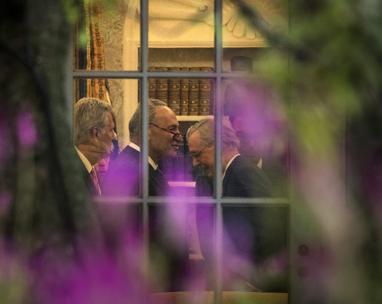 Senate Minority Leader Charles Schumer (D-NY) and Majority Leader Mitch McConnell (R-KY) are seen through a window of the Oval Office during a meeting with Donald Trump on Wednesday. (Photo by Bill O'Leary/The Washington Post)