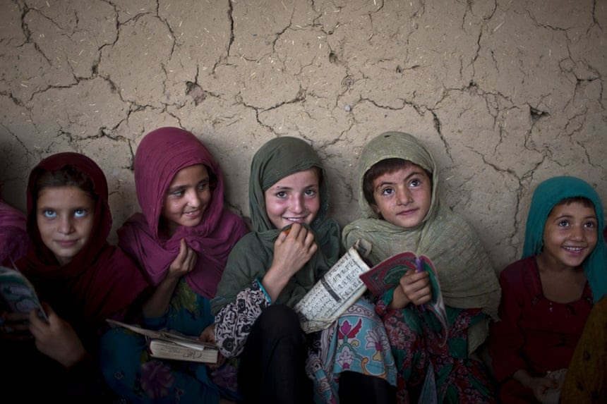 Afghan refugee girls listen to their teacher during their daily Madrassa, or Islamic school, at a mosque
