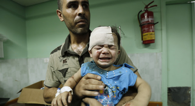 Un hombre coge en brazos a un niño herido tras el ataque de Israel a una escuela de la ONU.