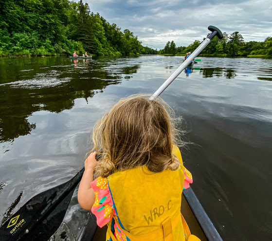 A little girl paddles at the front of a kayak wearing a yellow life jacket.