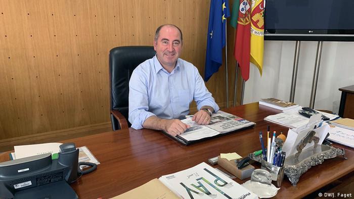 Homem de meia-idade sorridente, sentado a mesa de trabalho