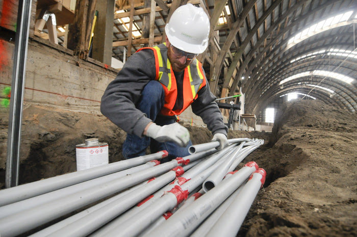 Steve Miller, a journeyman electrician with IBEW Local 48 and employee of Hybrid Tech, lays out electrical conduit on a grow facility being constructed in Hillsboro. (Sam Tenney/DJC)